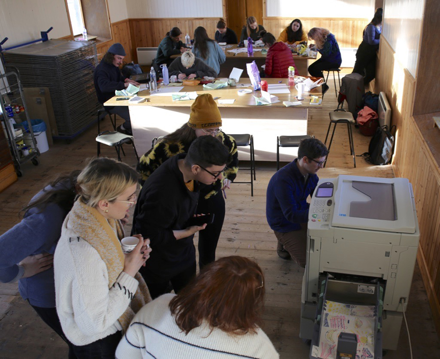 Groups of artists in a workshop, people drawing. Group of people standing around a photocopier