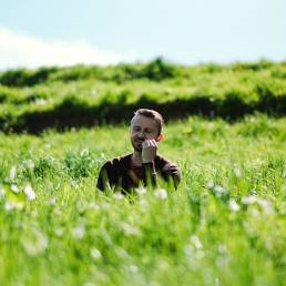 Phil Owen sitting in long grass, singing his hand is on his chin