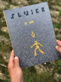 Front cover of SLUICE magazine, image on covertarmac with yellow 2m distance sign