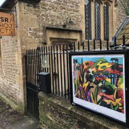 Noticeboard on railings outside of OSR Projects displaying colourful painting by Chris Burr