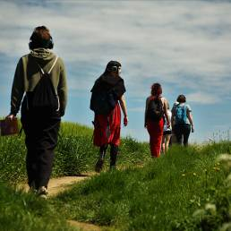 four people walking on a grassy path on th eedge of a field