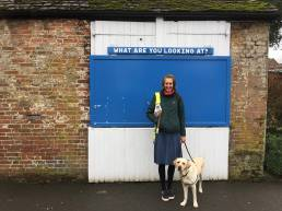angela wearing a green coat and blue skirt with flynn by her side, standing in front of a white wooden garage door with a blue noticeboard