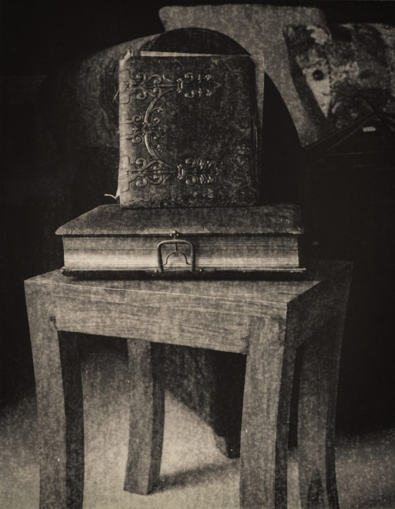 stack of old leatherbound books on a table with a grainy texture