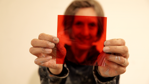Angela holding up a red square of plastic infront of her face